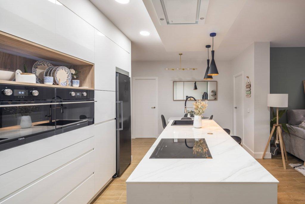 Cocina blanca con isla estratificada y panel de madera