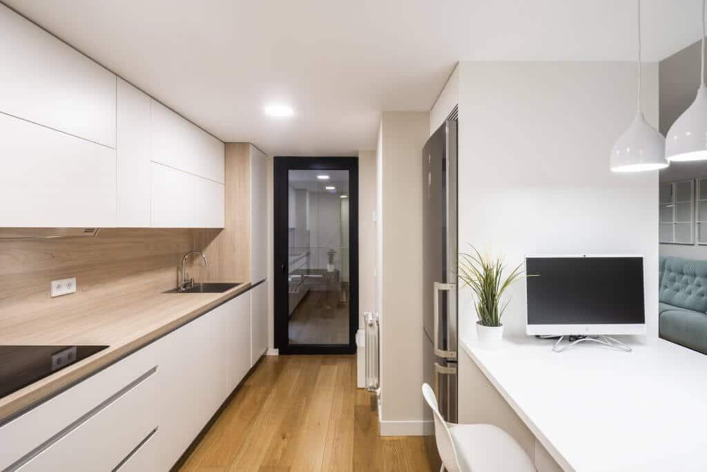 Vista alargada de cocina en madera y blanca con península