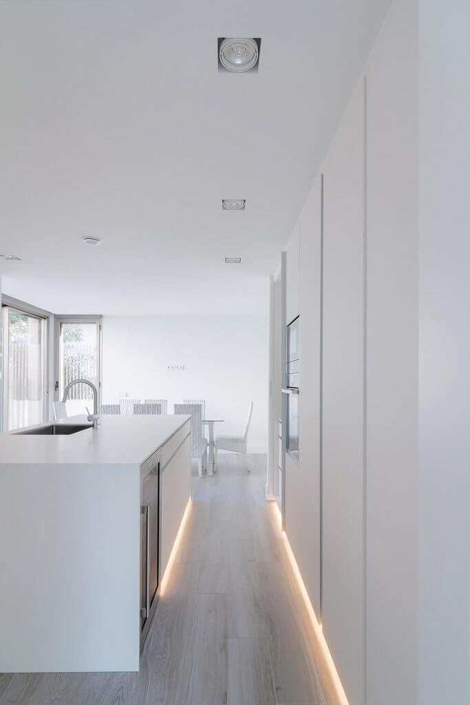 Cocina con isla blanca y concepta luces led