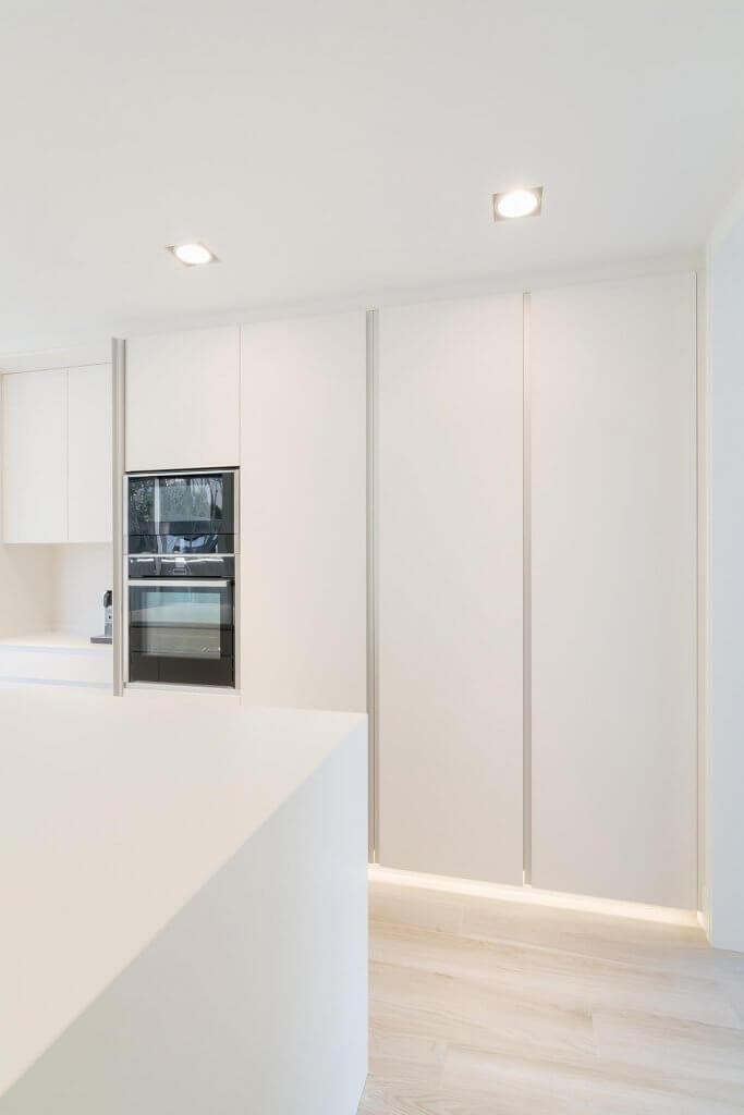 Cocina con isla blanca y concepta detalle luz led blanca