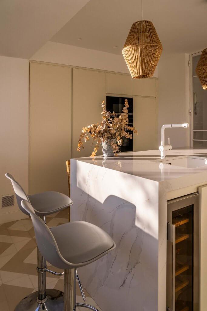 Cocina con isla polilaminada blanca con butacas grises
