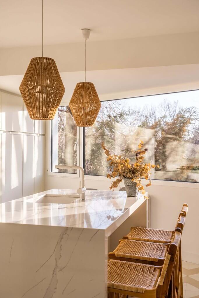 Cocina con isla polilaminada blanca detalle butacas y lámparas