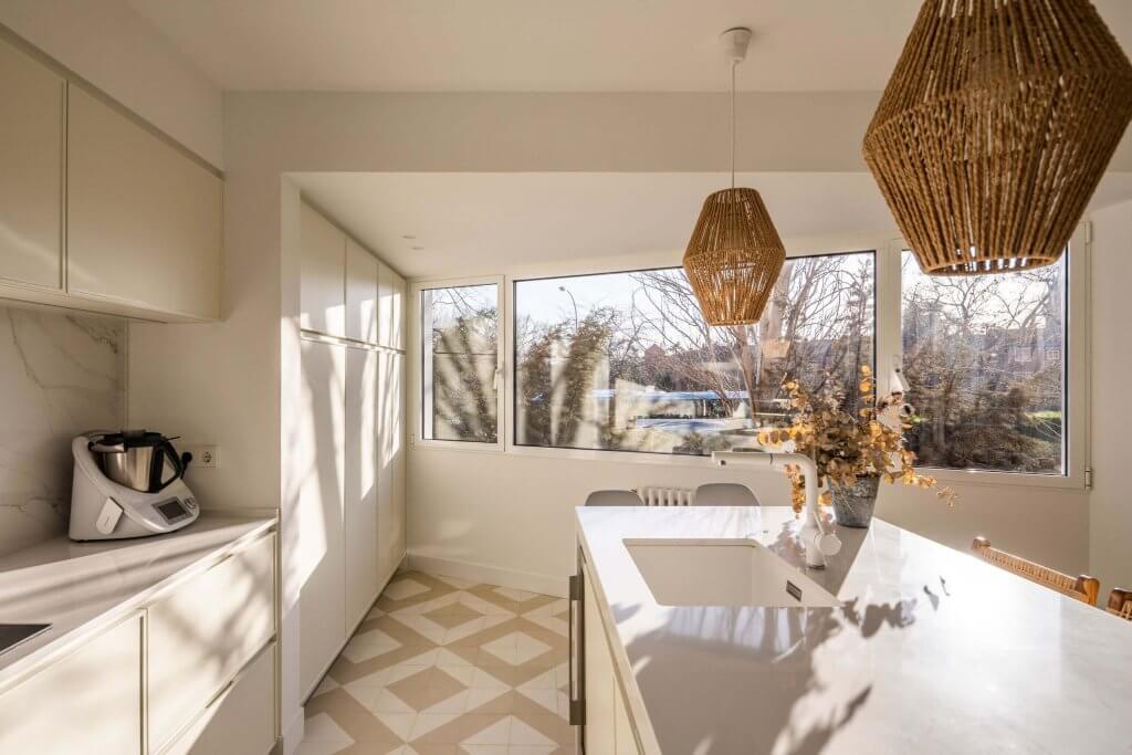 Cocina con isla blanca polilaminada y ventanal con vistas