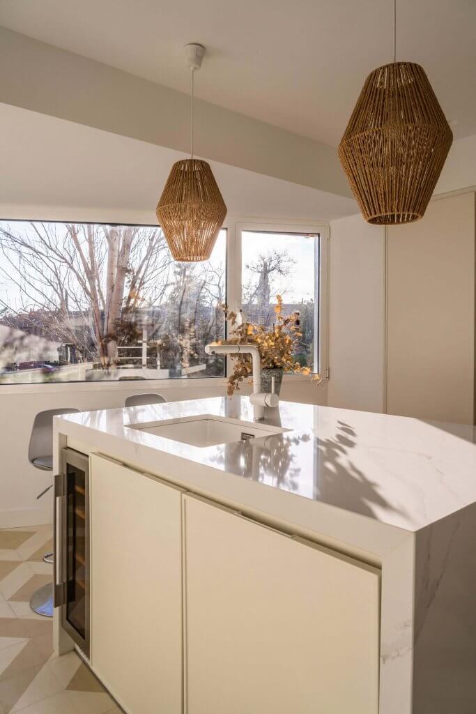 Cocina con isla polilaminada blanca con ventanal grande